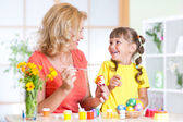 Mother showing to her child how to paint  Easter eggs — Stock Photo