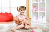 Cute little girl holding and embracing her doll — Stock Photo