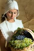 Woman with grapes in basket — Stock Photo