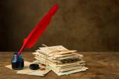 Red quill feather and old letters — Stock Photo