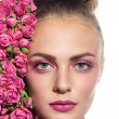 Woman with hair bun and pink roses — Stock Photo #75728901