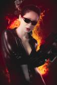 Sexy brunette woman in latex jumpsuit with heavy gun over fire b — Stock Photo