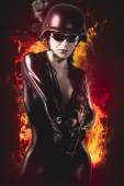 Sexy brunette woman in latex jumpsuit with heavy gun and helmet  — Stock Photo