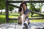 Young woman sitting under wooden fence — Stock Photo