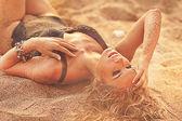 Beautiful girl  lying on the sand — Stock Photo
