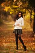 Elegant brunette posing in autumn park — Stock Photo