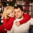 Young couple with gifts in front of Christmas tree — Stock Photo #59117133