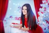 Young graceful brunette woman in christmas interior in white and red — Stock Photo