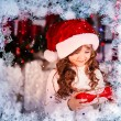 Excited little girl opening christmas present in front of the fir tree - closeup — Stock Photo #59439867