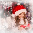 Excited little girl opening christmas present in front of the fir tree - closeup — Stock Photo #59439903