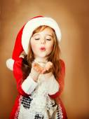 Happiness concept - happy girl in winter clothes blowing on palms — Stok fotoğraf