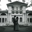Bride and groom standing near beautiful mansion — Stock Photo #54424671