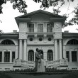 Bride and groom standing near beautiful mansion — Stock Photo #54424673