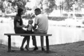 Family with child sitting on the bench — Stock Photo
