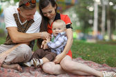 Young family with child in park — Stock Photo