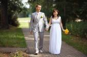 Bride and groom walking in park — Stock Photo