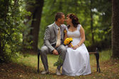 Bride and groom sitting on the bench — Stock Photo