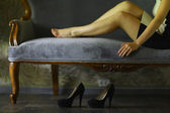 Beautiful woman legs on the sofa — Stock Photo