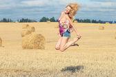 ブロンドの女性はフィールドにジャンプします — ストック写真