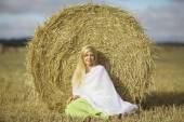 Blond woman sitting near the hay — ストック写真
