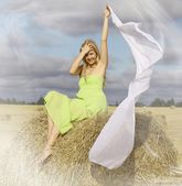 Blond woman sitting on the hay — Stock Photo