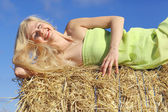 Blond woman lying on the hay — Stockfoto
