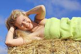 Blond woman lying on the hay — ストック写真