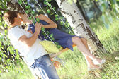 Man and a pregnant woman kissing on the swing — 图库照片