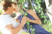 мужчина и беременная женщина, поцелуи на качели — Стоковое фото