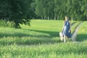 Girl walking along the road in a field — Stock Photo