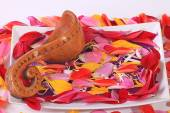Wooden spoon on multicolored flower petals — Stock Photo