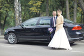 Wedding couple at car — Stok fotoğraf