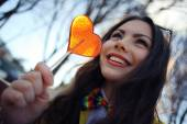 Girl holding heart shaped candy — Stock Photo