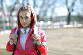 Girl in a sports jacket with a backpack — Stock Photo