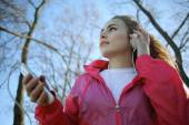 Girl walking in the park and listening music — Stock Photo