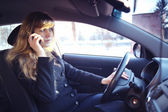 Girl driving the car  and talking the phone — Stock Photo