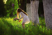 Girl collects flowers in sunny park — Stock Photo