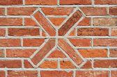 Masonry wall of bricks with a cross as decoration. — 图库照片