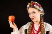 A young beautiful woman wearing a traditional Polish folk costume with an apple on a black background — Stock Photo