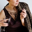 Beautiful woman with a cigarette and a glass of red wine — Stock Photo #64403743