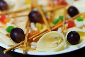 Mix of slices of cheese, olives, salt bread sticks — Stock Photo