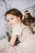 Little girl in bed playing — Stock Photo