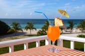 Close-up shot of the orange drink on the beach, sea and sky back — Stock Photo