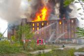 CELJE, SLOVENIA - OCTOBER 06, 2014: Firemen fight large-scale fire of historic industrial building Rakusev Mlin on October 6, 2014 in Celje. — Fotografia Stock