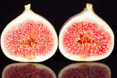 Fruits of sectioned fresh figs isolated on black  background — Stock Photo