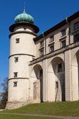 在新世界 Wisnicz 在波兰的城堡在蓝蓝的天空背景上查看 — 图库照片