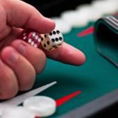 Backgammon player's hand holding the dice square — Fotografia Stock