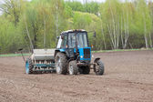 Tractor seeding the field — Stock Photo