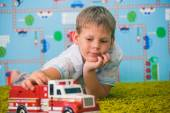 Young boy playing with car on the carpet — Stock Photo