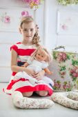 Young girl in a dress, playing with her doll — Stock Photo